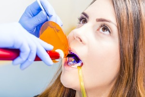 A dentist looking at a patient mouth and getting it ready for Teeth Bonding in Bloomington IL