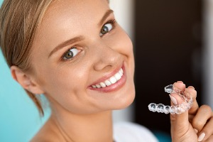Woman holding a retainer for Teeth Straightening in Bloomington IL